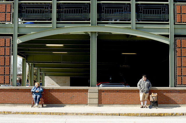 Dolores Ginn and Garry Brault, both of Lewiston, Maine, stand apart from one another as they wait for the bus at the Oak Street parking garage in downtown Lewiston, Maine, on Wednesday, March 18, 2020. Brault said that he just came from the grocery store where many of the shelves are bare. Ginn said that she is 86-years-old and not worried at all about the coronavirus pandemic. (Daryn Slover/Sun Journal via AP)