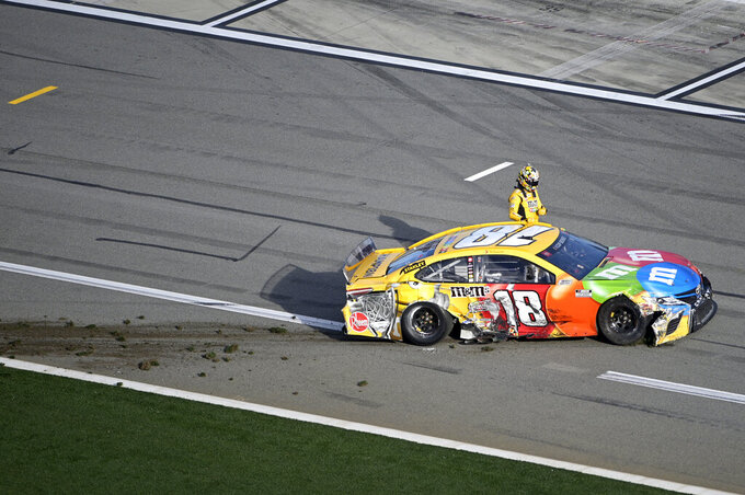 Kyle Busch (18) climbs out of his car after coming to a stop on pit road after colliding in Turn 4 during the NASCAR Daytona Clash auto race at Daytona International Speedway, Sunday, Feb. 9, 2020, in Daytona Beach, Fla. (AP Photo/Phelan M. Ebenhack)