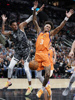 Phoenix Suns' Kelly Oubre, Jr. (3) reacts as the ball is knocked away by San Antonio Spurs' Dejounte Murray during the first half of an NBA basketball game, Friday, Jan. 24, 2020, in San Antonio. (AP Photo/Darren Abate)