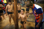 In this Feb 5, 2019, photo, a mallakhamb instructor Sachin Malekar, right, calms a child who made an unsuccessful attempt to climb the pole, at Shivaji Park in Mumbai, India. The word mallakhamb comes from malla, meaning wrestler, and khamb, or pole, and is a traditional training exercise for wrestlers in India. After centuries of being practiced in isolation in the subcontinent, mallakhamb is set to have its first international championship in Mumbai on Feb. 16 and 17. (AP Photo/Rafiq Maqbool)