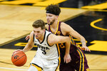 Iowa guard Jordan Bohannon (3) drives up court ahead of Minnesota guard Gabe Kalscheur, right, during the second half of an NCAA college basketball game, Sunday, Jan. 10, 2021, in Iowa City, Iowa. Iowa won 86-71. (AP Photo/Charlie Neibergall)