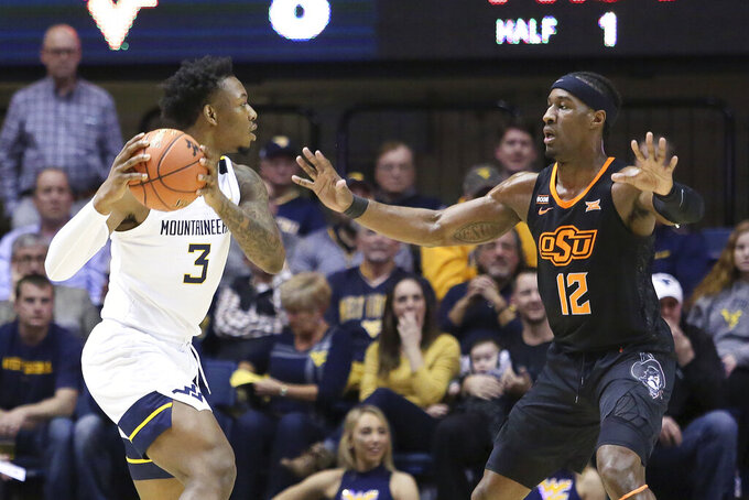 West Virginia forward Gabe Osabuohien (3) looks to pass the ball while defended by Oklahoma State forward Cameron McGriff (12) during the first half of an NCAA college basketball game Tuesday, Feb. 18, 2020, in Morgantown, W.Va. (AP Photo/Kathleen Batten)