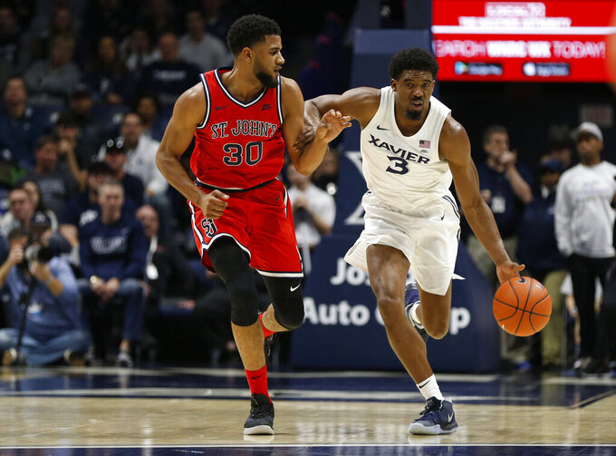 Xavier guard Quentin Goodin (3) is pressured by St. John's guard LJ Figueroa (30) as he drives the ball up court during the first half of an NCAA college basketball game, Sunday, Jan. 5, 2020, in Cincinnati. (AP Photo/Gary Landers)