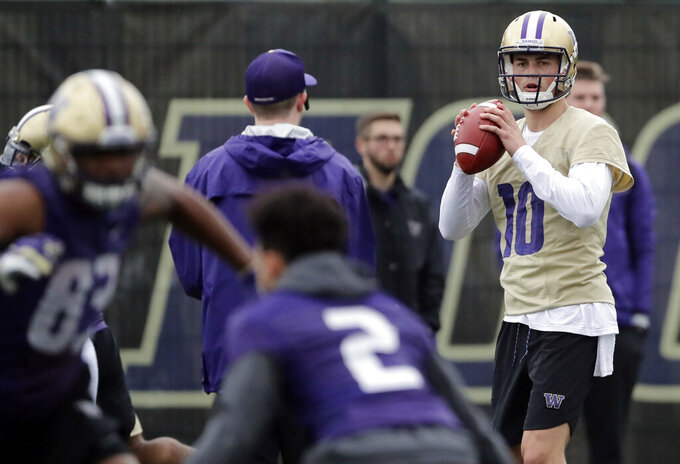 Washington quarterback Jacob Eason, right, looks to pass during the first day of spring NCAA college football practice, Wednesday, April 3, 2019, in Seattle. (AP Photo/Ted S. Warren)