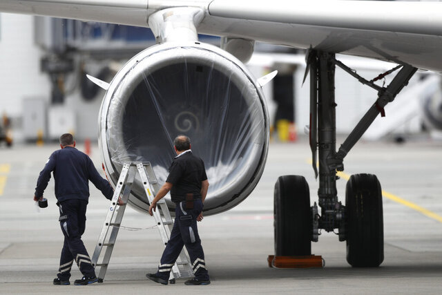 Technicians of the German airline Lufthansa work on an aircraft at the airport in Munich, Germany, Tuesday, May 26, 2020. Germany on Monday approved a 9 billion-euro ($9.8 billion) aid package for stricken airline Lufthansa to keep a major employer going through the turbulence of the coronavirus pandemic. (AP Photo/Matthias Schrader)