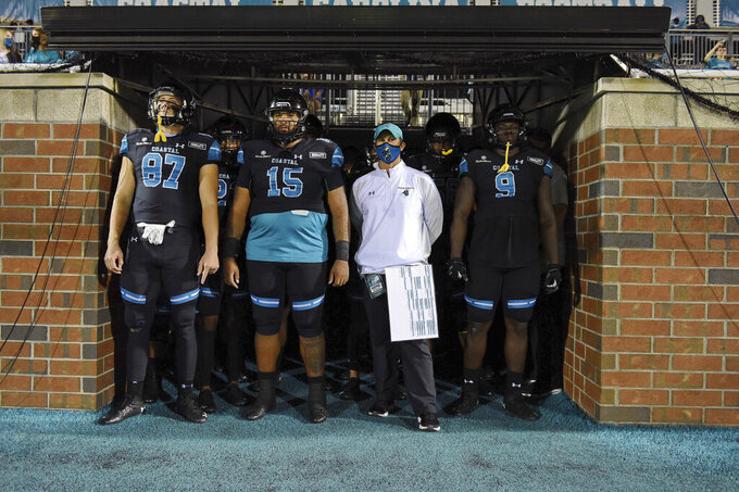 Coastal Carolina head coach Jamey Caldwell, second from right, waits with his team to take the field before an NCAA college football game against South Alabama, Saturday, Nov. 7, 2020, in Conway, S.C. (AP Photo/Richard Shiro)