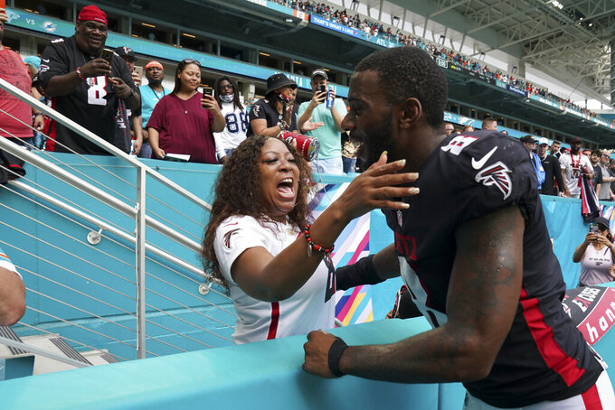 Atlanta Falcons tight end Kyle Pitts (8) is congratulated by a fan, as he leaves the field after the Falcons defeated the Miami Dolphins 30-28 in their NFL football game, Sunday, Oct. 24, 2021, in Miami Gardens, Fla. (AP Photo/Hans Deryk)