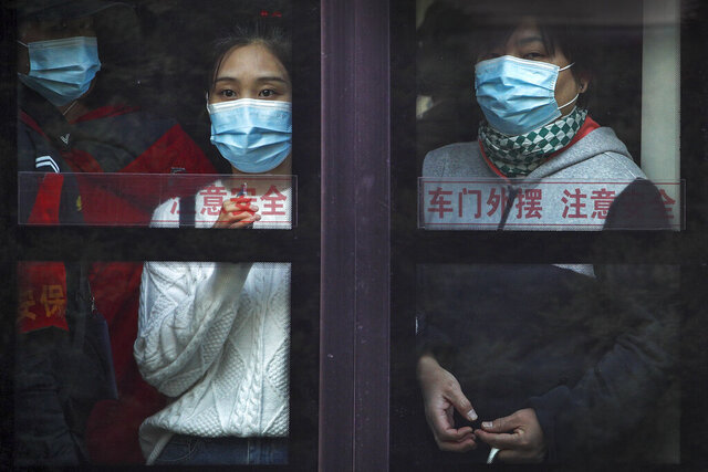 Commuters wearing face masks to help curb the spread of the coronavirus look out from a traveling bus during the morning rush hour in Beijing, Monday, Oct. 26, 2020. Schools and kindergartens have been suspended and communities are on lockdown in Kashgar, a city in China's northwest Xinjiang region, after more than 130 asymptomatic cases of the coronavirus were discovered. (AP Photo/Andy Wong)