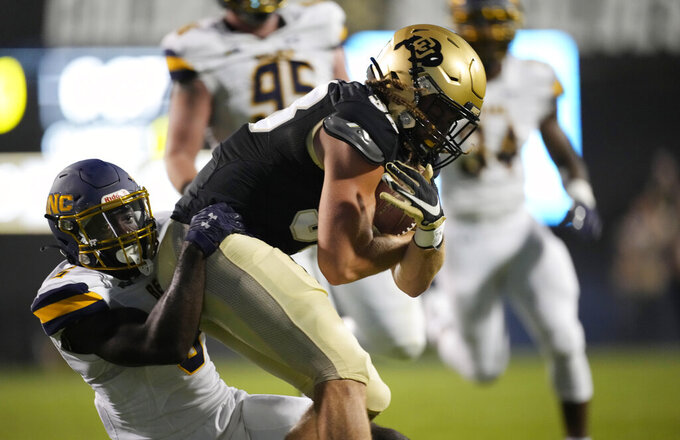 Colorado tight end Brady Russell, right, is dragged down by Northern Colorado linebacker Keyvon Lakes in the first half of an NCAA college football game Friday, Sept. 3, 2021, in Boulder, Colo. (AP Photo/David Zalubowski)