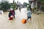 People carry their belongings as they wade through water in an area affected by flash floods in Luwu Utara, South Sulawesi province, Indonesia, Thursday, July 16, 2020. A number of people were killed and missing after heavy rains in the South Sulawesi province swelled rivers and send floodwaters, mud and debris across roads and into thousands of homes. (AP Photo/Khaizuran Muchtamir)