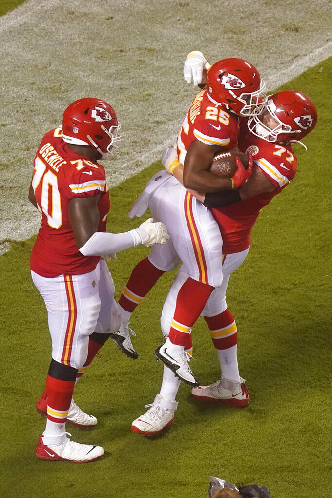 Kansas City Chiefs running back Clyde Edwards-Helaire (25) celebrates with Andrew Wylie (77) and Kelechi Osemele (70) after Edwards-Helaire scored a touchdown on a 27-yard run against the Houston Texans in the second half of an NFL football game Thursday, Sept. 10, 2020, in Kansas City, Mo. (AP Photo/Charlie Riedel)