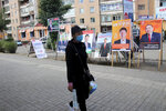 A resident carries groceries past posters and stands of various political party and independent candidates in the Songinokhairkhan district on the outskirts of Ulaanbaatar, Mongolia, Monday, June 22, 2020. Mongolia holds parliamentary elections on Wednesday, continuing a nearly 30-year democratic system in a vast but lightly populated country sandwiched between authoritarian regimes in Russia and China and beset by economic problems. (AP Photo/Ganbat Namjilsangarav)