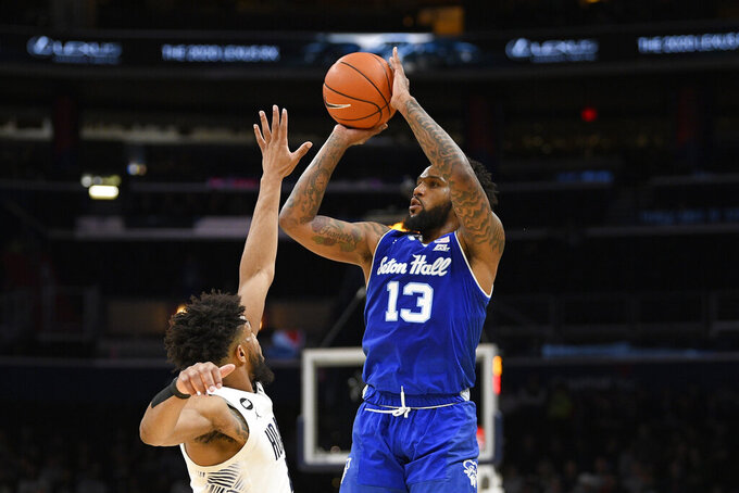 Seton Hall guard Myles Powell (13) shoots next to Georgetown guard Jagan Mosely, left, during the first half of an NCAA college basketball game, Wednesday, Feb. 5, 2020, in Washington. (AP Photo/Nick Wass)