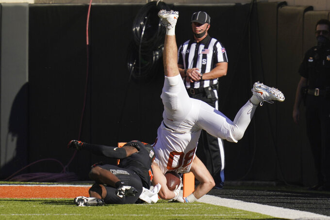 Texas tight end Cade Brewer (80) is upended by Oklahoma State safety Tanner McCalister, left, during the first half of an NCAA college football game in Stillwater, Okla., Saturday, Oct. 31, 2020. (AP Photo/Sue Ogrocki)