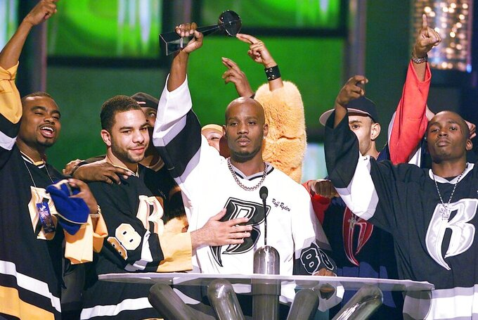 """FILE - DMX, center, accepts the R&B Album Artist of the Year during the 1999 Billboard Music Awards in Las Vegas, on Dec. 8, 1999. The family of rapper DMX says he has died at age 50 after a career in which he delivered iconic hip-hop songs such as """"Ruff Ryders' Anthem."""" A statement from the family says the Grammy-nominated rapper died at a hospital in White Plains, New York, """"with his family by his side"""" after being placed on life support for the past few days. He was rushed to a New York hospital from his home April 2. (AP Photo/Laura Rauch, File)"""