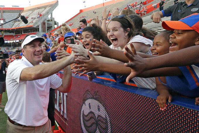 Florida head coach Dan Mullen greets fans as he leaves the field after defeating Towson in an NCAA college football game, Saturday, Sept. 28, 2019, in Gainesville, Fla. (AP Photo/John Raoux)