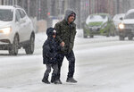 Wearing their Minnesota Twins hats, Jimmy Cordova and his grandpa, Christian, hold hands as they cross East 7th Street Friday, Jan. 17, 2020, in St. Paul, Minn., as snow falls on their way to CentroMex Supermercado. (Jean Pieri/Pioneer Press via AP)