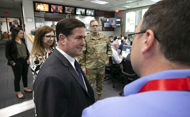 FILE - In this March 18, 2020, file photo, Arizona Gov. Doug Ducey, foreground left, talks to Matt Heckard, right, assistant director of preparedness with the state's Department of Emergency and Military Affairs, as members of DEMA work responding to the coronavirus pandemic, in the DEMA operations center at the Arizona National Guard Papago Park Military Reservation in Phoenix. Maj. Gen. Michael T. McGuire, background center, the director of DEMA, and Wendy Smith-Reeve, stand next to Ducey. Smith-Reeve, director of the Arizona Division of Emergency Management, submitted her resignation Saturday, March 29. The state's emergency operations will now be directed by Maj. Gen. Michael T. McGuire. (David Wallace/The Arizona Republic via AP, Pool, File)