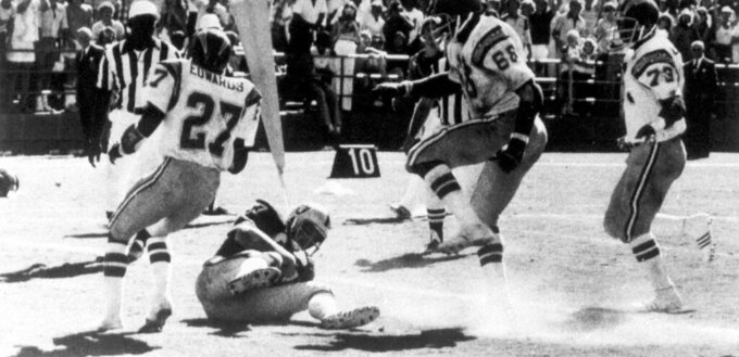 FILE - In this Sept. 11, 1978, file photo, Oakland Raiders' Dave Casper falls in the endzone for a touchdown against the San Diego Chargers on the final play of a football game, in San Diego.  The stage was set in San Diego when the Raiders had the ball at the Chargers 14, trailing 20-14 with 10 seconds left. Ken Stabler dropped back to pass and was pressured by Chargers linebacker Woodrow Lowe. With nowhere to throw the ball, Stabler either fumbled or pushed the ball forward on purpose, depending on which side of the rivalry is telling the story. Teammate Pete Banaszak then knocked the ball further ahead from about the 13-yard line as it rolled toward the end zone. Tight end Dave Casper kicked the ball forward at the 5 and then fell on it in the end zone with no time remaining. (Thane McIntosh/The San Diego Union-Tribune via AP)