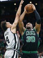 Boston Celtics' Guerschon Yabusele (30) shoots against San Antonio Spurs' Derrick White (4) during the first half of an NBA basketball game in Boston, Sunday, March 24, 2019. (AP Photo/Michael Dwyer)