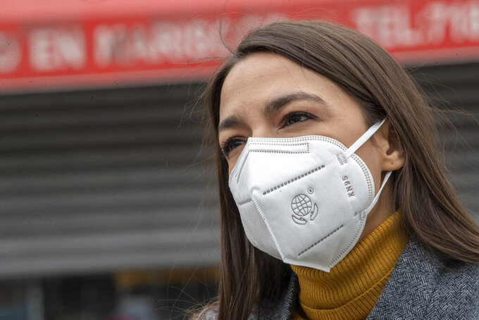 FILE - In this Tuesday, April 14, 2020 file photo, Rep. Alexandria Ocasio-Cortez, D-N.Y., wears a face mask during a news conference to call on FEMA to grant approval for Disaster Funeral Assistance to help families in lower-income communities and communities of color across New York amid the COVID-19 coronavirus pandemic, in the Corona neighborhood of the Queens borough of New York. On Friday, June 26, 2020, The Associated Press reported on stories circulating online incorrectly asserting a May 20 tweet sent and later deleted by Ocasio-Cortez argues that governors should keep businesses closed until after the presidential election because economic recovery will help get President Donald Trump re-elected. The tweet was fabricated. It does not appear in archived versions of Ocasio-Cortez's Twitter feed or in databases that track deleted tweets by politicians. (AP Photo/Mary Altaffer)