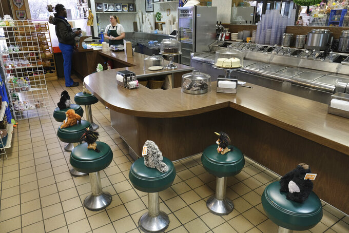 FILE - In this March 16, 2020, file photo, stuffed animals resting on the stools at Bischoff's, an ice cream parlor in Teaneck, N.J., serve as a gentle reminder that customers are not allowed to sit down.  (AP Photo/Seth Wenig, File)