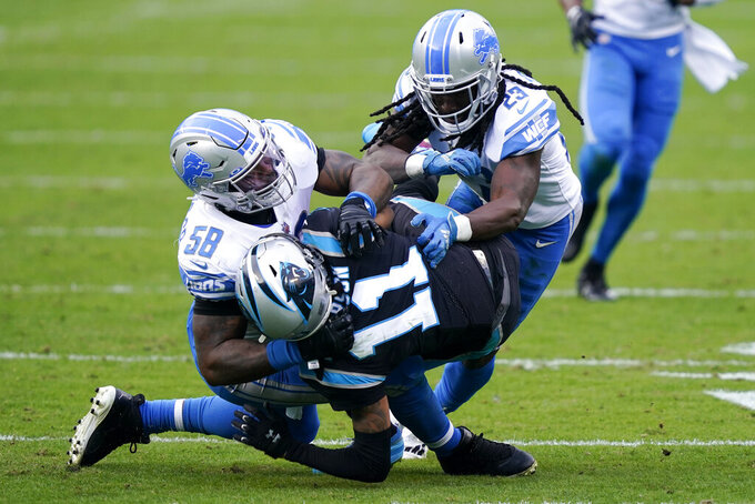 Detroit Lions outside linebacker Jamie Collins, left, and cornerback Desmond Trufant tackle Carolina Panthers wide receiver Robby Anderson during the first half of an NFL football game Sunday, Nov. 22, 2020, in Charlotte, N.C. (AP Photo/Gerry Broome)