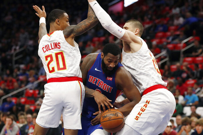 Detroit Pistons center Andre Drummond loses control of the ball as Atlanta Hawks forward John Collins (20) and center Alex Len, right, defend during the first half of an NBA basketball game Thursday, Oct. 24, 2019, in Detroit. (AP Photo/Carlos Osorio)