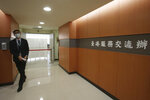 A staff member walks out of the Taiwan Hong Kong Service Exchange Office after its opening ceremony in Taipei, Taiwan, Wednesday, July 1, 2020.  Taiwan officially opened the specialized office on Wednesday to support Hong Kong people seeking to move to Taiwan after China's passage of a national security law for Hong Kong. (AP Photo/Chiang Ying-ying)