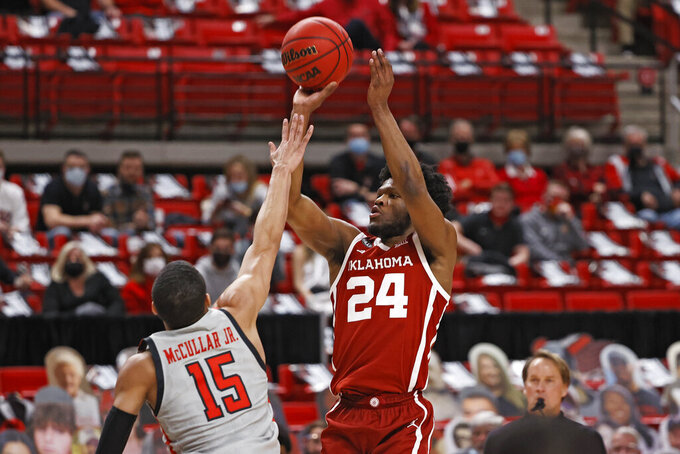 Oklahoma's Elijah Harkless (24) shoots ball over Texas Tech's Kevin McCullar (15) during the first half of an NCAA college basketball game Monday, Feb. 1, 2021, in Lubbock, Texas. (AP Photo/Brad Tollefson)