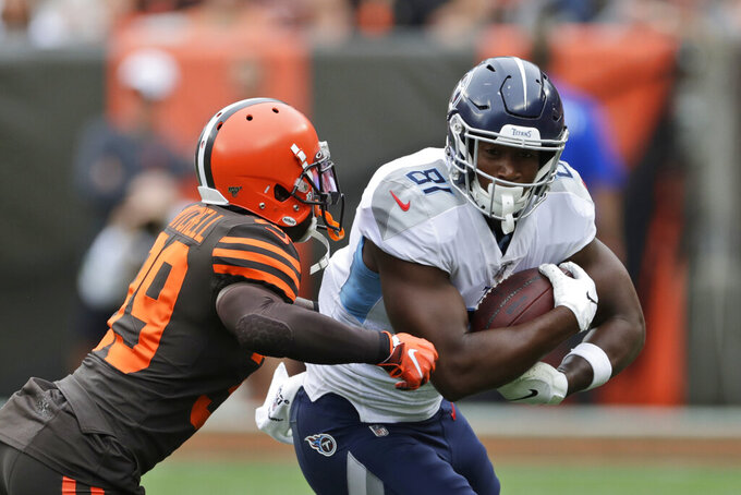 Cleveland Browns cornerback Terrance Mitchell (39) tackles Tennessee Titans tight end Jonnu Smith (81) after a pass reception during the first half in an NFL football game Sunday, Sept. 8, 2019, in Cleveland. (AP Photo/Ron Schwane)