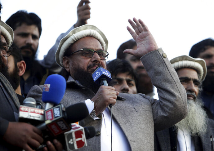 File - In this Feb. 5, 2019 file photo, Hafiz Saeed, chief of Pakistani religious group Jamaat-ud-Dawa, addresses a rally in Lahore, Pakistan. Pakistan has re-imposed a ban on two charities run by a U.S.-wanted suspect behind the 2008 Mumbai terror attacks. The Interior Ministry said on Friday that the country's top security body decided on the ban during a meeting held by Prime Minister Imran Khan. (AP Photo/K.M. Chaudary, File)