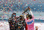 Mercedes driver Lewis Hamilton of Britain, cwnter, is sprayed champagne at the podium on the podium of the Formula One Turkish Grand Prix at the Istanbul Park circuit racetrack in Istanbul, Sunday, Nov. 15, 2020. Racing Point driver Sergio Perez of Mexico, right, finished second and Ferrari driver Sebastian Vettel of Germany, finished third. (AP Photo/Kenan Asyali, Pool)