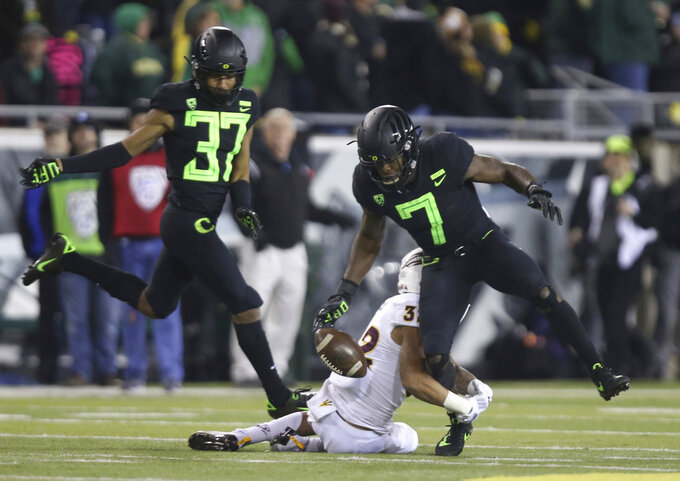 Oregon's Ugochukwu Amadi, right, loses control of a punt us he is tackled by Arizona State's Paul Lucas during the fourth quarter of an NCAA college football game Saturday, Nov. 17, 2018, in Eugene, Ore. (AP Photo/Chris Pietsch)