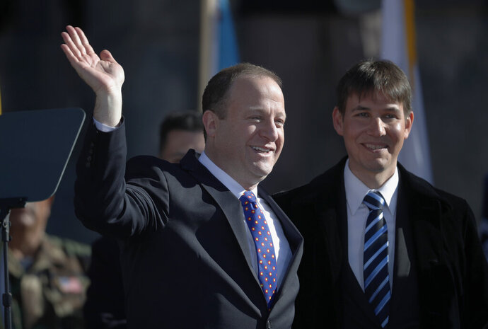 FILE - In this Tuesday, Jan. 8, 2019 file photo, Colorado Gov. Jared Polis, left, joins his partner, Marlon Reis, in acknowledging the crowd after Polis took the oath of office during the inauguration ceremony in Denver. Colorado Gov. Jared Polis has tested positive for the coronavirus. Polis and his partner, Marlon Reis, both have COVID-19 and are asymptomatic, the governor said in a statement Saturday night, Nov. 28, 2020.  (AP Photo/David Zalubowski, Pool)