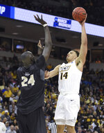 VCU's Marcus Santos-Silva (14) shoots over Central Florida's Tako Fall (24) during the first half of a first-round game in the NCAA men's college basketball tournament Friday, March 22, 2019, in Columbia, S.C. (AP Photo/Richard Shiro)