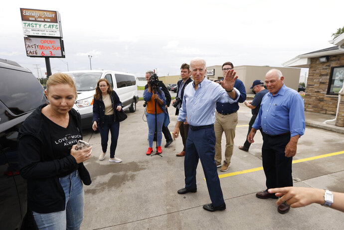 Democratic presidential candidate former Vice President Joe Biden waves to local residents after a stop at the Tasty Cafe, Wednesday, June 12, 2019, in Eldridge, Iowa. (AP Photo/Charlie Neibergall)
