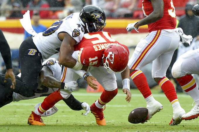 Kansas City Chiefs quarterback Patrick Mahomes (15) fumbles the ball for a turnover during a tackle by Baltimore Ravens linebacker Kenny Young (40) during the second half of an NFL football game in Kansas City, Mo., Sunday, Sept. 22, 2019. (AP Photo/Ed Zurga)