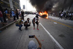 An Atlanta Police Department vehicle burns as people pose for a photo during a demonstration against police violence, Friday, May 29, 2020, in Atlanta. The protest started peacefully earlier in the day before demonstrators clashed with police. The Memorial Day death of George Floyd in police custody in Minneapolis has sparked protests nationwide. (AP Photo/Mike Stewart)