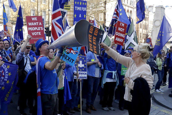 FILE - In this Wednesday, Feb. 27, 2019 file photo, a supporter of Britain's departure from the European Union, at right, holds a placard up in front of supporters of remaining in the EU, including Stop Brexit Man, Steve Bray, with his foghorn, outside Parliament in London. Five years ago, Britons voted in a referendum that was meant to bring certainty to the U.K.'s fraught relationship with its European neigbors. Voters' decision on June 23, 2016 was narrow but clear: By 52 percent to 48 percent, they chose to leave the European Union. It took over four years to actually make the break. The former partners are still bickering, like many divorced couples, over money and trust. (AP Photo/Matt Dunham, File)