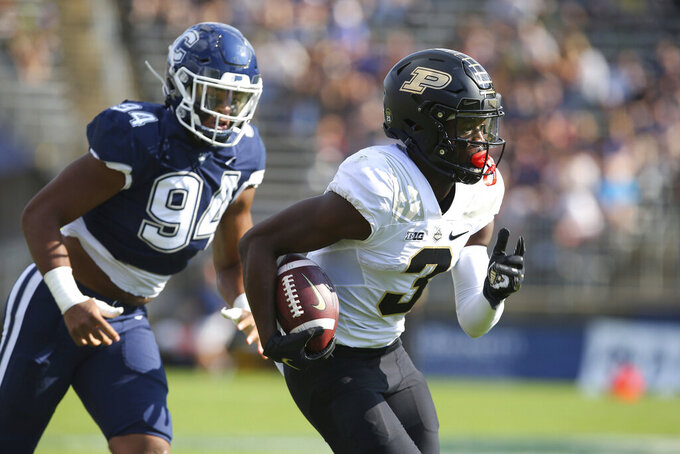 Purdue wide receiver David Bell (3) is pursued by Connecticut defensive lineman Nick Harris (94) during the first half of an NCAA football game on Saturday, Sept. 11, 2021, in East Hartford, Conn. (AP Photo/Stew Milne)
