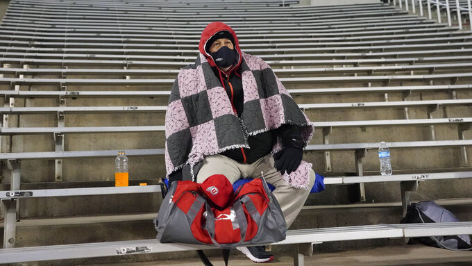 A Utah fan sits in the stands of Rice-Eccles Stadium before an NCAA college football game between Southern California and Utah on Saturday, Nov. 21, 2020, in Salt Lake City. (AP Photo/Rick Bowmer)