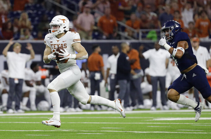 Texas wide receiver Jake Smith races to the end zone after making a catch past Rice defensive back Prudy Calderon (4), for a 53-yard touchdown during the first half of an NCAA college football game Saturday, Sept. 14, 2019, in Houston. (AP Photo/Eric Gay)