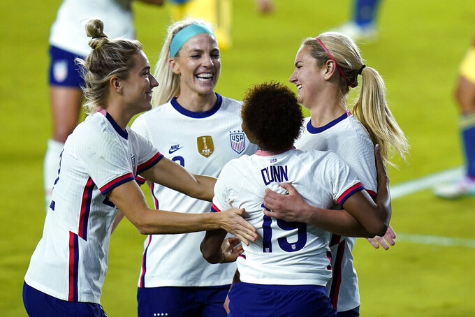 U.S. midfielder Lindsey Horan, right, is congratulated, after scoring a goal against Colombia, by midfielder Kristie Mewis, left, midfielder Julie Ertz, center, and defender Crystal Dunn, second from right, during the second half of an international friendly soccer match Friday, Jan. 22, 2021, in Orlando, Fla. (AP Photo/John Raoux)