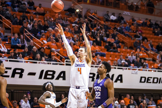 Oklahoma State's Thomas Dziagwa shoots a 3-pointer next to TCU's RJ Nembhard (22) during an NCAA college basketball game Wednesday, Feb. 5, 2020, in Stillwater, Okla. (Devin Lawrence/Tulsa World via AP)