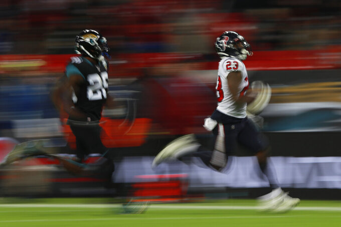 Houston Texans running back Carlos Hyde (23) runs the ball against Jacksonville Jaguars free safety Jarrod Wilson (26) during the second half of an NFL football game at Wembley Stadium, Sunday, Nov. 3, 2019, in London. (AP Photo/Ian Walton)