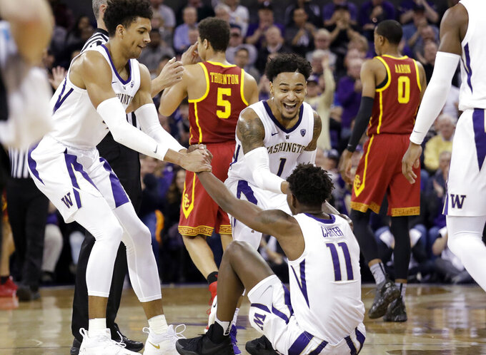 Washington's Matisse Thybulle, left, and David Crisp (1) rush to help up Nahziah Carter (11) after Carter was fouled by a Southern California player during the first half of an NCAA college basketball game Wednesday, Jan. 30, 2019, in Seattle. (AP Photo/Elaine Thompson)