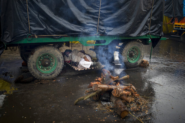 A farmer lies under the belly of a tractor trolley next to a bonfire as they block a major highway in a protest against new farm laws while it rains at the Delhi-Uttar Pradesh state border, India, Monday, Jan. 4, 2021. (AP Photo/Altaf Qadri)