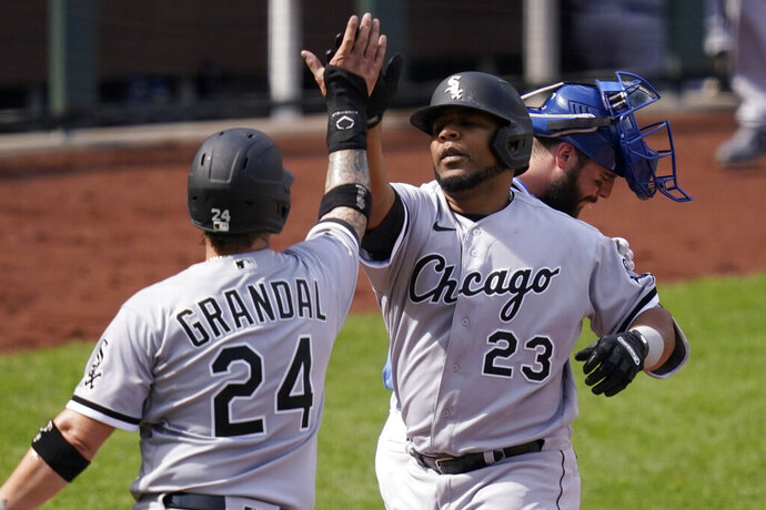 Chicago White Sox designated hitter Edwin Encarnacion (23) is congratulated by teammate Yasmani Grandal (24) after his three-run home run during the seventh inning of a baseball game against the Kansas City Royals at Kauffman Stadium in Kansas City, Mo., Sunday, Sept. 6, 2020.(AP Photo/Orlin Wagner)
