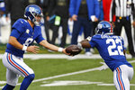 New York Giants quarterback Daniel Jones (8) hands off the ball to running back Wayne Gallman (22) during the first half of NFL football game against the Cincinnati Bengals, Sunday, Nov. 29, 2020, in Cincinnati. (AP Photo/Aaron Doster)